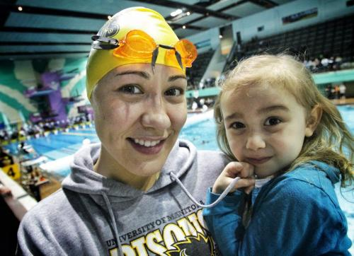 Kimberly Moors, 26, with her daughter, Mila Gaslard, 3, swims for the University of Manitoba Bisons at the Prairie Winter Invitational Sunday morning.  121202 December 02, 2012 Mike Deal / Winnipeg Free Press