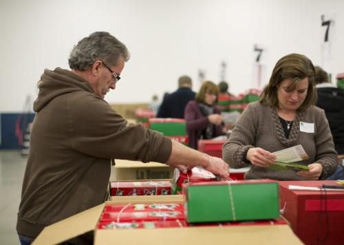 Henry Friesen (L) of Steinbach, Manitoba helps pack boxes at the Samaritan's Purse operation during the Christmas season in Calgary, Alberta, December 3, 2012. In 1993, Operation Christmas Child grew and was adopted by Samaritan's Purse, a Christian organization run by Franklin Graham. To date, Operation Christmas Child has collected and distributed over 94 million shoe box gifts worldwide.  Each shoe box gift is filled with hygiene items, school supplies, toys, and candy, is given to children regardless of gender, race, religion, or age. Photograph by Todd Korol for The Winnipeg Free Press