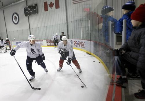 Colin Wilson (from Winnipeg) with the  Nashville Predators carries the puck against Winnipeg Jet Olli Jokinen  at the NHLPA  practice at the MTS Iceplex Wednesday morning as young and old fans wait for the lockout to end. (WAYNE GLOWACKI/WINNIPEG FREE PRESS) Jan. 2 2012