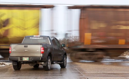 Waiting for a Train - A truck waits for a long train pulling grain cars to pass Thursday afternoon at Sturgeon Road and Saskatchewan Ave. Standup photo– January 10, 2013   (JOE BRYKSA / WINNIPEG FREE PRESS) rail crossing