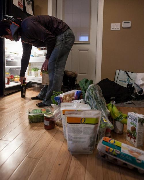 Jets forward Jim Slater piles his organic food haul on the floor as he organizes his fridge after first shop of the hockey season before training camp. (Melissa Tait / Winnipeg Free Press)