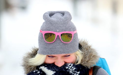 Brandon Sun 05022013 Olga Antipova, originally from Saint Petersburg, Russia, walks along Princess Ave. sporting colourful sunglasses on her toque on a cold Tuesday afternoon. Antipova came to Brandon to learn english and now works here. (Tim Smith/Brandon Sun)