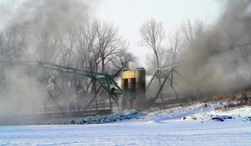 The smoke clears after the St. Jean Baptiste bridge was demolished around 9 AM Saturday morning in front of a gathering of townspeople and local residents.  130216 February 16, 2013 Mike Deal / Winnipeg Free Press