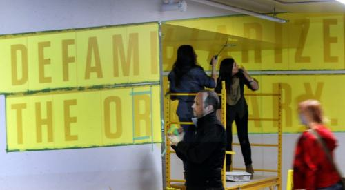U of M Interior Design Masters student John deWolf tapes off the projected letters that will be painted for the quote defamiliarize the ordinary by American graphic designer Paul Rand in the underground tunnel by the University Centre at the University of Manitoba Thursday morning.  John won the Tunnel Vision competition, his idea was to change the experience in a generic tunnel walkway into an extra ordinary experience using anamorphic typography so the letters distort as you pass through the walkway. He is assisted by fellow students Jennifer Norrie,left, and Jessica Kost.  (WAYNE GLOWACKI/WINNIPEG FREE PRESS) Feb. 21 2013