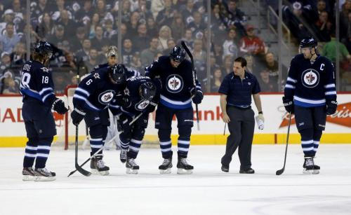 Winnipeg Jets' Bryan Little (18), Ron Hainsey (6), Zach Bogosian (44), a trainer and Andrew Ladd (16) assist Blake Wheeler (26), middle, off the ice after he went down in the second period of NHL hockey against the Washington Capitals' at MTS Centre, Saturday, March 2, 2013. (TREVOR HAGAN/WINNIPEG FREE PRESS)