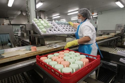 Teresita Mayuga takes recently cleaned mugs from the red tray and puts them, colour coded, into the custom made white trays and also keeps an eye on the conveyor belt for mugs to toss into the washer (just below the white tray) during a tour of the Regional Distribution Facility at the WRHA Nutrition and Food Services Centre at 345 De Baets Street in St. Boniface.  130312 - Tuesday, March 12, 2013 -  (MIKE DEAL / WINNIPEG FREE PRESS)