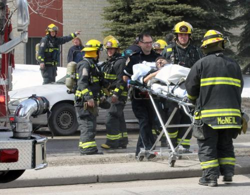 Fire and EMT crews remove a person with smoke inhalation from a apartment fire at 1164 Jefferson Ave near noon – Fire crews knocked the blaze down quickly-Standup photo- April 11, 2013   (JOE BRYKSA / WINNIPEG FREE PRESS)