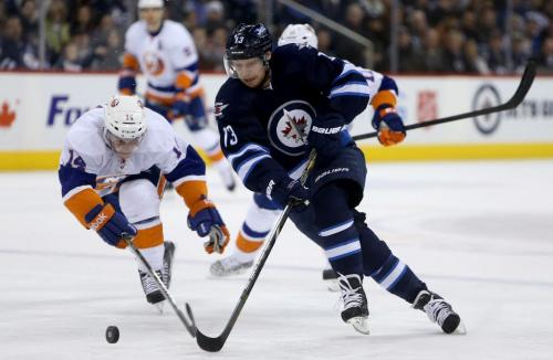 Winnipeg Jets' Kyle Wellwood (13) skates around New York Islanders' Thomas Hickey (14) before scoring his second goal of the second period during NHL action at MTS Centre in Winnipeg, Saturday, April 20, 2013. (TREVOR HAGAN/WINNIPEG FREE PRESS)