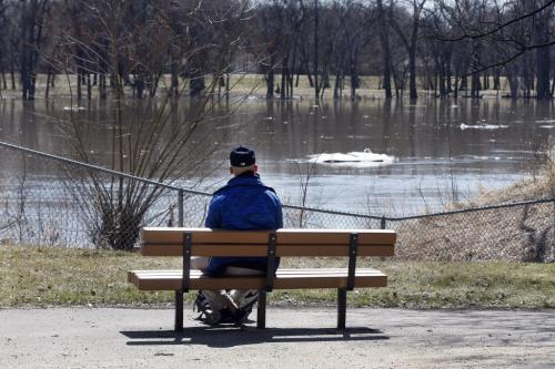 Stdup – Watching the River Flow – Jeremy Botelho relaxes  in the sun at Kildonan Park watching the  swollen Red River and floating ice pass by . KEN GIGLIOTTI / May 3  2013 / WINNIPEG FREE PRESS