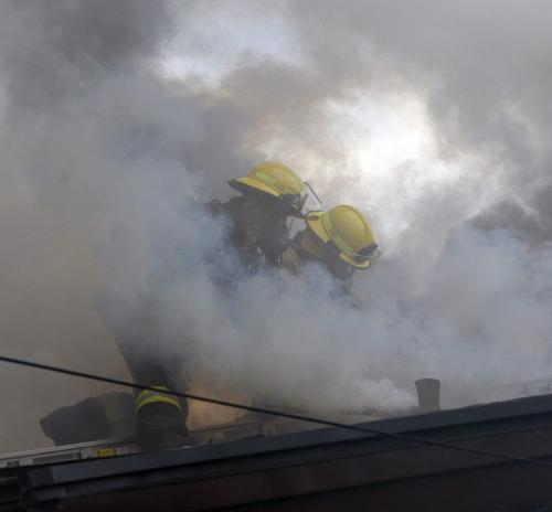 Firefighter battle heavy smoke of roof top -House fire , bungalow at  Foxdale ave and the corner of Delbrook Cres. near Rothesay and Chief Peguis Trail , the fire started in the cieling and the entire roof structure is billowing smoke from several holes cut by the fire crews trying to fight the fire  KEN GIGLIOTTI / JUNE 5 2013 / WINNIPEG FREE PRESS