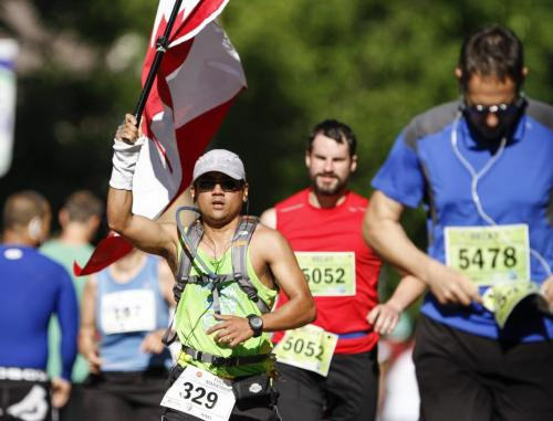 A full marathon runner carries a Canadian flag enroute past Laura Secord School in Wolseley during the Manitoba Marathon in Winnipeg on Sunday, June 16, 2013. (JESSICA BURTNICK/WINNIPEG FREE PRESS)