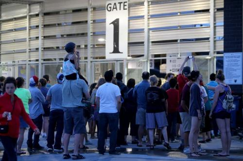 Those without tickets watch Taylor Swift through the gates at Investors Group Field, Saturday, June 22, 2013. (TREVOR HAGAN/WINNIPEG FREE PRESS)