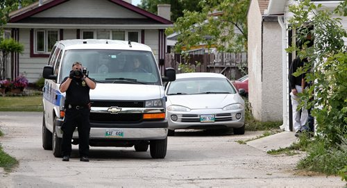 A WPS Identification Unit Officer takes photos of the alley behind the home on Bondar Bay where Winnipeg Police Service say a 19 year-old male was found unresponsive after a fight at another home in the neighbourhood. The male victim was pronounced dead after being transported from the house.  130721 July 21, 2013 Mike Deal / Winnipeg Free Press