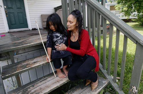 Edee O'Meera with grand son Damien age 3  on ther cottage front steps -Misty Lake Lodge is home to many aboriginal flood evacuee from the Lake Manitoba Flood , the  lodge  has not been paid for accommodating evacuees – Randy Turner story-  KEN GIGLIOTTI / JULY 22 2013 / WINNIPEG FREE PRESS