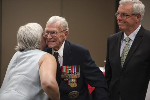 George  Peterson (centre), the sole surviving member of the Arden Seven, receives a hug from Christine Melnick, MLA for Riel, during the dedication of a new park plaza in honour of seven comrades who grew up on Arden Ave. in Winnipeg. They volunteered, fought and were captured during the Battle of Hong Kong during the Second World War in 1941. The Arden Seven Interpretive Plaza, to be located in Jules Mager Park in St. Vital, was announced at the Viscount Gort Hotel today by Premier Greg Selinger (right) and Mayor Sam Katz. It commemorates comrades Fred Abrahams, twins Morris and George Peterson, and brothers Alfred, Edward and Harry Shayler, all of whom survived the battle of Hong Kong. Friday, August 16, 2013.  (OLIVER SACHGAU) (JESSICA BURTNICK/WINNIPEG FREE PRESS)