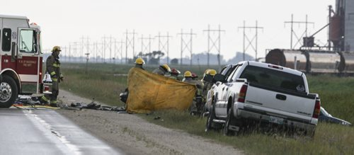 Emergency personnel remove the body of a crash victim from the vehicle. A crash involving two vehicles occurred on Highway 3 about 2-kms West of Brunkild, Man. today around 4 p.m. One infant and one child were among the victims. Two people were dead at the scene, and the others transported to hospital. Saturday, August 24, 2013. (JESSICA BURTNICK/WINNIPEG FREE PRESS)