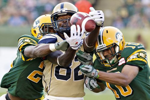Winnipeg Blue Bombers' Terrence Edwards #82 misses the catch as Edmonton Eskimos' Marcell Young #23 and Donovan Alexander #10 defend during second half action in Edmonton, Alta., on Saturday September 14, 2013. THE CANADIAN PRESS/Jason Franson