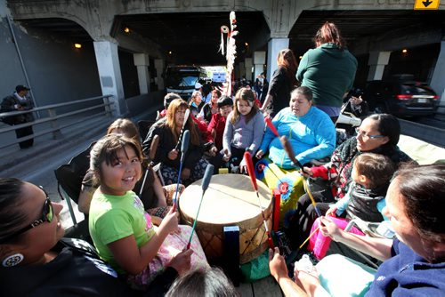 Seven year old Ryleigh Todd-Moore sits on her moms lap while singing and drumming along with a drumming group on a float as the group makes  their way under the Main Street bridge Saturday during the 7th annual Medicine Walk which raises awareness of the abuse of children.    Sept  21,, 2013 Ruth Bonneville Winnipeg Free Press