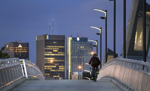 A commuter heads across the recently opened new active transportation bridge for cyclists, pedestrians and other non-motorized users over the Red River along side of the Disraeli  Bridge Monday morning.  Wayne Glowacki / Winnipeg Free Press Sept. 23 2013