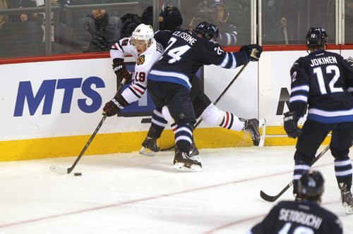 Winnipeg Jet #24 Clitsome checks Blackhawk #19 Toews during the 3rd  period of play  Saturday afternoon at MTS Centre. November 02,,  Winnipeg Jets vs Chicago Blackhawks at MTS Centre Saturday. 2013 Ruth Bonneville / Winnipeg Free Press