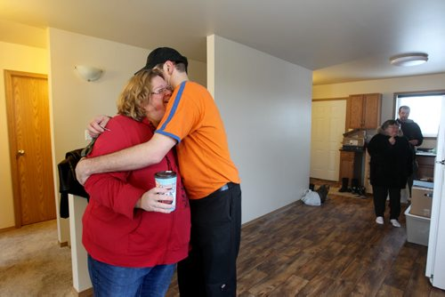Shannon and Rene Van De Kaere embrace just before they move in their belongings to their new home on moving day.  Photo Essay on the Van De Kaere family (including  Cadence, Shannon, Rene and Brendon) finally moving into their Habitat home just  in time for Christmas.  Dec 16, 2013 Ruth Bonneville / Winnipeg Free Press