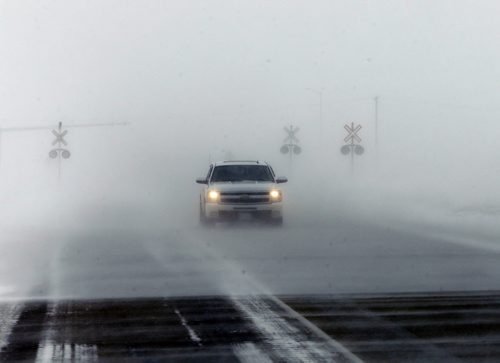 Stdup Weather - Truck appears through the white out conditions on Perimeter Hwy 100 near McGillivray Blvd.Stdup Weather – high winds and blowing snow  are causing white out conditions on the Perimeter Hwy and open area coming into town causing many cars to go off the road  . JAN. 16 2014 / KEN GIGLIOTTI / WINNIPEG FREE PRESS