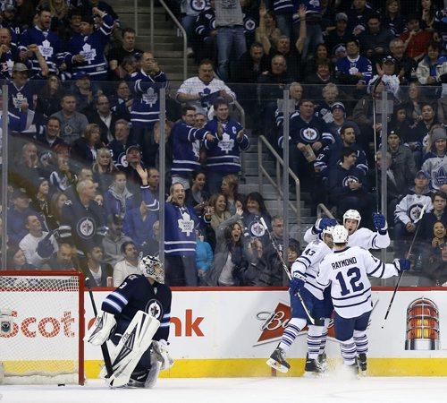 Winnipeg Jets' goaltender Ondrej Pavelec (31) looks on as Toronto Maple Leafs' Nazem Kadri (43), Mason Raymond (12) and Troy Bodie (40) celebrate after Bodie scored during second period NHL hockey action at MTS Centre in Winnipeg, Saturday, January 25, 2014. (TREVOR HAGAN/WINNIPEG FREE PRESS)