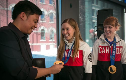 Olympic curling champions Kaitlyn Lawes (centre) and Dawn McEwen laugh with fan Eric Dozin and his reaction to their gold medals after an interview at the Free Press News Café Tuesday. The team, minus skip Jones, met and signed autographs with dozens of fans at the Café a day after arriving back home from Sochi, Russia. Feb 25, 2014 (Mike Deal / Winnipeg Free Press)