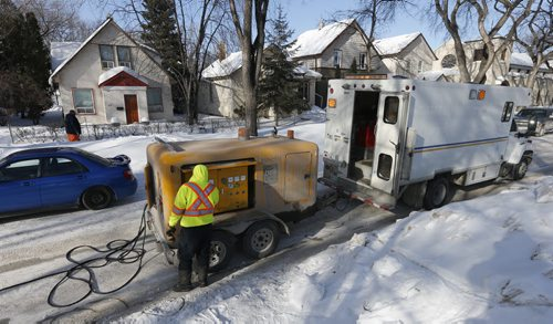 City crew heats frozen water line running under Mulvey Ave using a heavy duty battery connected to metal water pipes -LOCAL - A City of Wpg crew was thawing frozen water pipes on Mulvey Ave . The process uses electrical current  from a DBH battery to thaw  frozen pipe  that ran under  the street  to the  home without water . The home owner has been without water for ten days . See video Bart Kives story .  FEB. 26 2014 / KEN GIGLIOTTI / WINNIPEG FREE PRESS