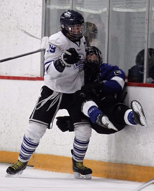 River East Kodiaks' Nolan Wisniewski crushes Oak Park Raiders' Jeremy Hope into the boards during their AAAA Provincial High School Hockey game at Gateway Arena, Saturday, March 15, 2014. (TREVOR HAGAN/WINNIPEG FREE PRESS)