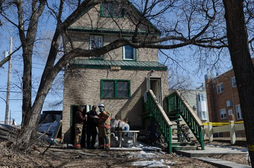 Fire officials stand outside of a home on the 300 block of Enfield Crescent near Marion Street.  The basement resident died as a result of the fire.  The cause of the early morning fire is under investigation.  EMILY CUMMING / WINNIPEG FREE PRESS APRIL 16, 2014