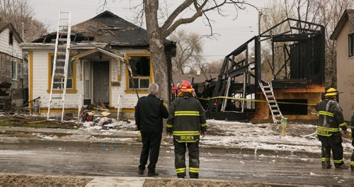 Winnipeg Fire Paramedic investigators at the scene of a fire damaged home on Jefferson Avenue near Scotia Street. In total four houses were damaged, fire and police continue to investigate.  140519 - Monday, May 19, 2014 - (Melissa Tait / Winnipeg Free Press)