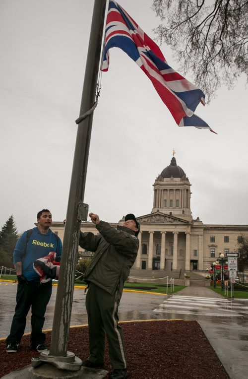 The Union Jack is raised at the Manitoba Legislature by protection services officer Eustaquio Tadeo, with help from Tyler MacMartin, in advance of Prince Charles and his wife Camilla, Duchess of Cornwall's, visit to Winnipeg on Wednesday.   140519 - Monday, May 19, 2014 - (Melissa Tait / Winnipeg Free Press)