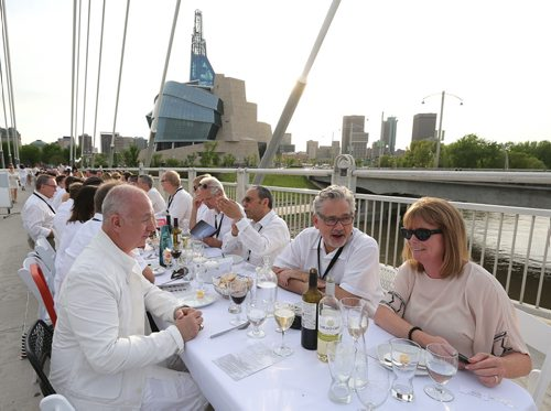 From left, Albert Paquette, Vern Reimer and Aine Culligan enjoy themselves at the Table for 1200 event on the Esplanade Riel Bridge on Sat., May 31, 2014. The event was an initiative of StorefrontMB and 5468796 Architecture, and was created to highlight Winnipeg's emerging design scene by bringing together architecture, design and the culinary arts. The prairie-themed food for the 'pop up' outdoor dining experience was provided by local chefs Mandel Hitzer from Deer + Almond and Joe Kalturnyk from RAW Gallery, along with Ben Kramer from Diversity Food Services. Photo by Jason Halstead/Winnipeg Free Press