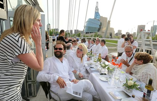 Table for 1200 event organizers Anna Hurme (third left) and Sasa Radulovic (second left) chat with diners at the VIP table on the Esplanade Riel Bridge on Sat., May 31, 2014. The event was an initiative of StorefrontMB and 5468796 Architecture, and was created to highlight Winnipeg's emerging design scene by bringing together architecture, design and the culinary arts. The prairie-themed food for the 'pop up' outdoor dining experience was provided by local chefs Mandel Hitzer from Deer + Almond and Joe Kalturnyk from RAW Gallery, along with Ben Kramer from Diversity Food Services. Photo by Jason Halstead/Winnipeg Free Press