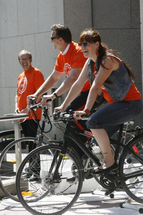 Kayla Chafe, a member of the Bike Week Winnipeg Steering Committee and Winnipeg Police Inspector Gord Friesen take their turn on the bikes that were powering the sound system for the announcement at City Hall  the first annual Bike Week Winnipeg will take place this year from June 16 - 22.  Bike Week Winnipeg will offer seven days of bike programming, including the 7th annual Bike to Work Day on Friday, June 20.  see  city news release. Wayne Glowacki / Winnipeg Free Press June 10 2014