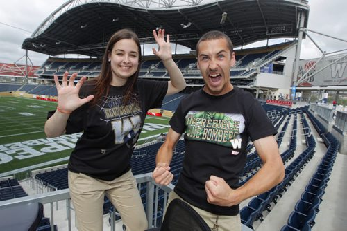 Bomber Store employees Samantha LaPointe and Quinn Smith ham it up with the new Marvel comic character Winnipeg Blue Bomber T-Shirts at Investors Group Centre. BORIS MINKEVICH / WINNIPEG FREE PRESS  June 25, 2014