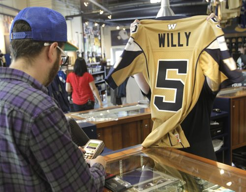 Winnipeg Blue Bomber QB Drew Willy #5 jerseys are the big seller at the Bomber Store at Investors Group Field Friday the day after the season opener victory over Toronto. Season ticket holder Bryce Twerdochlib purchases one.   Paul Wicek story Wayne Glowacki / Winnipeg Free Press June 27 2014