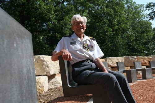 George Peterson, the last surviving member of the group of seven local Arden Ave war veterans from the Battle of Hong Kong, sits in one of the 7 chairs of honour  at the new Jules Mager Park in St. Vital where a special ribbon cutting ceremony was held Saturday morning. Minister Kevin Chief and St. Vital Councillor Brian Brian Mayes help Mr. Peterson out of his wheelchair and onto one of the seven chairs. See Ashley Prest story. July 12, 2014 Ruth Bonneville / Winnipeg Free Press