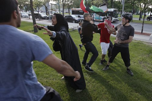 """July 14, 2014 - 140714  -  An Israel supporter is escorted away after provoking peaceful Palestinian supporters by yelling """"stop hiding behind your children"""" as they hold a rally at the Manitoba Legislature Monday, July 14, 2014. John Woods / Winnipeg Free Press"""