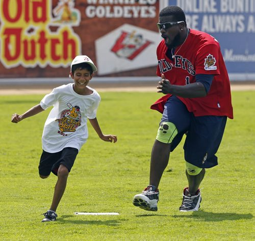 Stdup- Fun and Run . Wpg Goldeyes  outfielder #1 Reggie Abercrombie  chases  Luke D'Souza  around third base  during a base running drill  at the  McDonald's All-Star Skills Camp put on for kids at Shaw Park Tuesday afternoon in conjuction with the All-Star   game tonight at the park . Goldeyes players coached baseball skills  to the kids at various stations . July 29 2014 / KEN GIGLIOTTI / WINNIPEG FREE PRESS