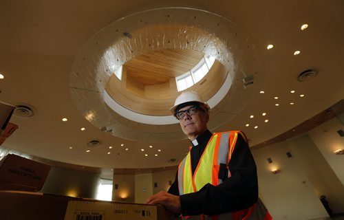 Faith .Rev. Darren Gurr  at his new parish church St. Gianna  Beretta Molla  Roman catholic Church still under construction  , a brand new $14 million Roman catholic Church  on Columbia in  features  circular  worship area with alter in the centre of the space , workers  finishing area for glass bottomed baptismal in the  modern architecture  church .  Aug 12 2014 / KEN GIGLIOTTI / WINNIPEG FREE PRESS