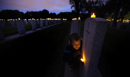 Candles Glow, row on row....7 yr old Connor Chaulk checks out names on the rows of veteran graves at Brookside Cemetery Wednesday evening at the Candle Light Vigil held to mark the Anniversary of the start of WW2. Connor doesn't have any veteran relatives in Brookside but made a point of remembering his Great Grandfather, a second world war veteran is buried in Stonewall's cemetery. See release. September 10, 2014 - (Phil Hossack / Winnipeg Free Press)