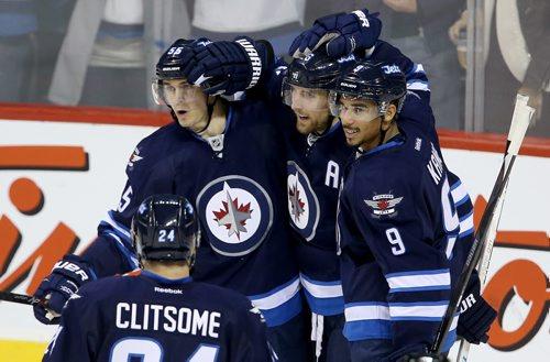 Winnipeg Jets' Grant Clitsome (24), Mark Scheifele (55), Blake Wheeler (26) and Evander Kane (9) celebrate after Wheeler scored against the Calgary Flames' during the first period of NHL hockey action in Winnipeg, Saturday, October 4, 2014. (TREVOR HAGAN/WINNIPEG FREE PRESS)