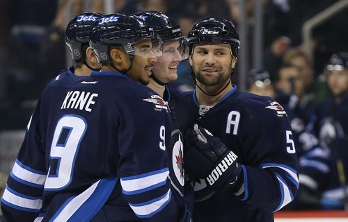 Winnipeg Jets' Mark Scheifele (55), Evander Kane (9), Jacob Trouba (8) and Mark Stuart (5) celebrate after Trouba scored against the Calgary Flames' during the second period of preseason NHL hockey action in Winnipeg, Saturday, October 4, 2014. (TREVOR HAGAN/WINNIPEG FREE PRESS)