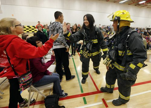 STDUP . Fire Prevention Week starts Oct 5 to11  .Gr. 7 teacher Meghan McOmber (in WFS turnout gear)  and WFS firefighter Marcel Laporte give high fives to students at the assembly .The  to  the pubic is reminded to check their smoke alarm and carbon monoxide detector batteries as well a review  home escape plans in case of fire .This year  kick off was held at Bernie Wolfe School other activities during the week include WFS Fire Drill across the city schools on Friday  and Saturday  the Fire paramedic stations are open to the public for tours as well as Fire Chief for a Day event . Oct. 6 2014 / KEN GIGLIOTTI / WINNIPEG FREE PRESS