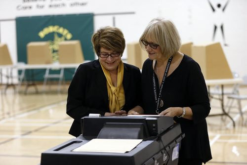 Election Day Winnipeg Mayoral Candidate (left) Judy Wasylycia-Leis casts her vote into vote machine  just after 9am at Luxton School polling station  About a dozen people lined up before 8am at Luxton School polling station to vote . Oct. 22 2014 / KEN GIGLIOTTI / WINNIPEG FREE PRESS