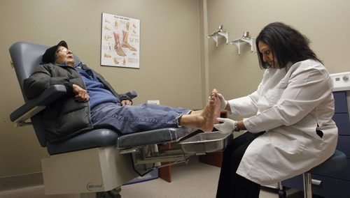Dr. Tejel Patel, a volunteer Podiatrist with a  Siloam Mission guest Thursday after the official opening of the new podiatry room in the Saul Sair Health Centre part of the Siloam Mission. Podiatry and foot care services are essential to those experiencing homelessness, many cope with diabetes, circulation issues, or other conditions which stress foot health. The new podiatry room provides a professional, modern, and well-equipped clinical setting for these critical services. Several devoted podiatrists and foot nurses volunteer their time and expertise to Siloam Mission clients every week. The Canadian Footwear and the Foot Health Centre have  been  providing quality footwear and custom orthotics for patient referrals. The facility has been established thanks to the efforts of Dr. Tejel Patel and her husband,  Anis Khan, generous donations from Fortress Real Developments, MADY Development Corp., the Mennonite Brethren Collegiate Institute's Youth in Philanthropy Committee, with help from dedicated volunteer, Chantel  Blunderfield. Wayne Glowacki / Winnipeg Free Press Nov. 27  2014