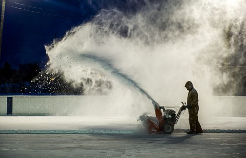 141129 Winnipeg - DAVID LIPNOWSKI / WINNIPEG FREE PRESS  John Young uses a snow blower to clear Friday nights' snowfall off of the hockey rink at Sir John Franklin Community Club Saturday evening. John has been volunteering his time, and using vacation time for the love of ice making for 13 years.