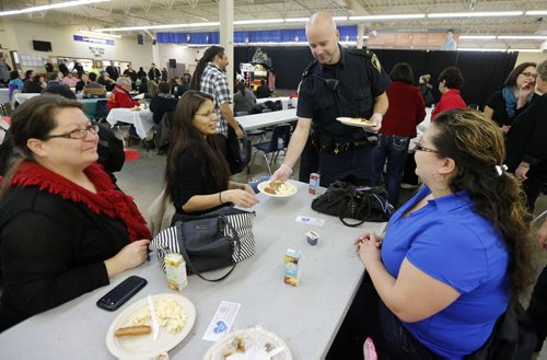 Stdup SERVES and Protects , Cst. Wilkinson of the WPS serves to breakfast to  LtoR Sherri Sinclair , Gloria Cook and right Chrissy Hansen was one of many police officers and cadets on hand to serve breakfast at the early morning  Indian and Metis Friendship Centre  breakfast fund raiser. Dec. 9 2014 / KEN GIGLIOTTI / WINNIPEG FREE PRESS